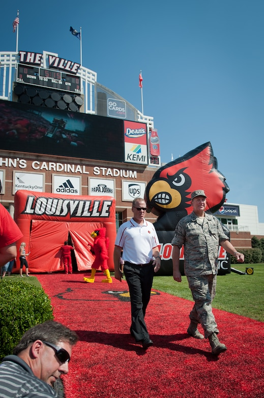 Kentucky's adjutant general, Maj. Gen. Edward Tonini (right), walks onto the field at Papa John's Cardinal Stadium in Louisville, Ky., Sept. 7, 2013, as part of Military Appreciation Day events held in conjunction with the University of Louisville-Eastern Kentucky University football game. Tonini executed the coin toss to begin the game. (U.S. Air National Guard photo by Maj. Dale Greer)