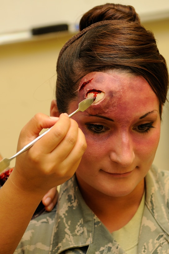 U.S. Air Force Staff Sgt. Evelyn Sanchez-Jalomo, 18th Dental Squadron dental laboratory craftsman, applies fake blood to simulate a head wound on Senior Airman Jessica Ashe, 18th Force Support Squadron assistant sports director, during a local operational readiness exercise on Kadena Air Base, Japan, Sept. 11, 2013. The simulated wounds are made to look as realistic as possible to ensure personnel respond more accurately while treating the victim. (U.S. Air Force photo by Senior Airman Marcus Morris)