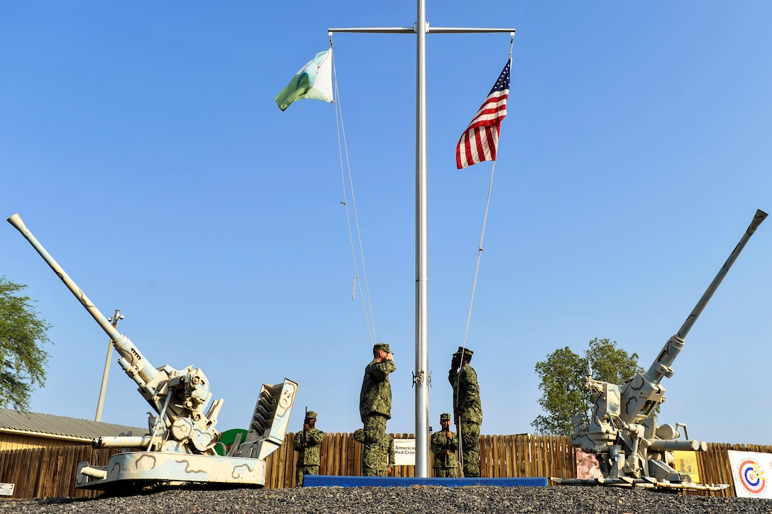 An honor guard detail salutes the U