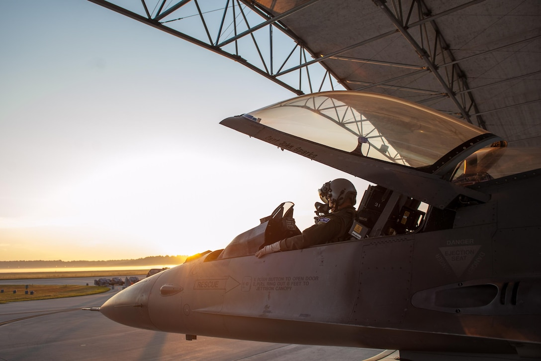 Maj. Ryan Corrigan sits in the cockpit of an F-16 Fighting Falcon during sunrise, Sept. 9, 2013, at McEntire Joint National Guard Base, S.C. Members of the 169th Fighter Wing are conducting a certified readiness evaluation, which assesses their ability to operate safely and efficiently in a deployed chemical combat environment.  Corrigan is with the 157th Fighter Squadron, South Carolina Air National Guard. (U.S. Air National Guard photo/Staff Sgt. Jorge Intriago)