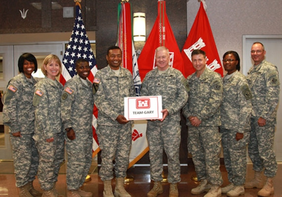 "Corps of Engineers commander Lt. Gen. Thomas Bostick, Corps chaplain Col. Phillip Wright and staff members hold a ""Team Gary"" sign in June at Corps headquarters in Washington."