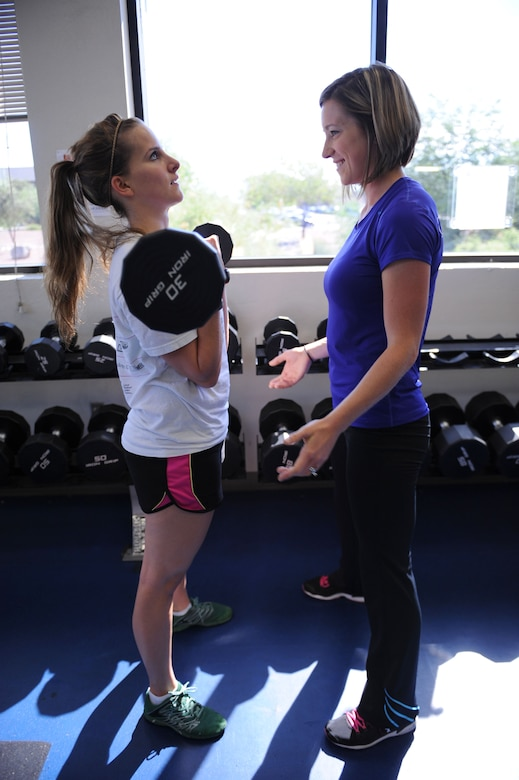 U.S. Air Force Senior Airman Katherine Sample, 355th Security Forces Squadron visitor center clerk, lifts a barbell at the Benko Fitness Center under the guidance of Kayla Pevehouse, Benko Fitness Center personal trainer, at Davis-Monthan Air Force Base, Ariz., Sept. 10, 2013. Receiving instruction, exercise or nutritional, from a licensed personal trainer can help improve physical fitness, which can help Airmen strengthen the physical pillar of Comprehensive Airman Fitness. (U.S. Air Force photo by Staff Sgt. Courtney Richardson/Released)