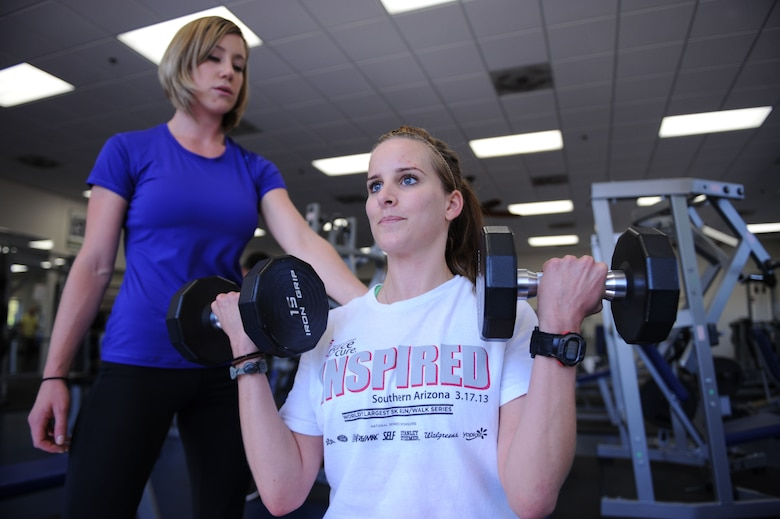 U.S. Air Force Senior Airman Katherine Sample, 355th Security Forces Squadron visitor center clerk, lifts dumb bells at the Benko Fitness Center during her personal training session with Kayla Pevehouse, Benko Fitness Center personal trainer, at Davis-Monthan Air Force Base, Ariz., Sept. 10, 2013.  For more information or assistance building your personal physical fitness, contact your unit fitness monitor, Health and Wellness Center or a personal trainer. (U.S. Air Force photo by Staff Sgt. Courtney Richardson/Released)