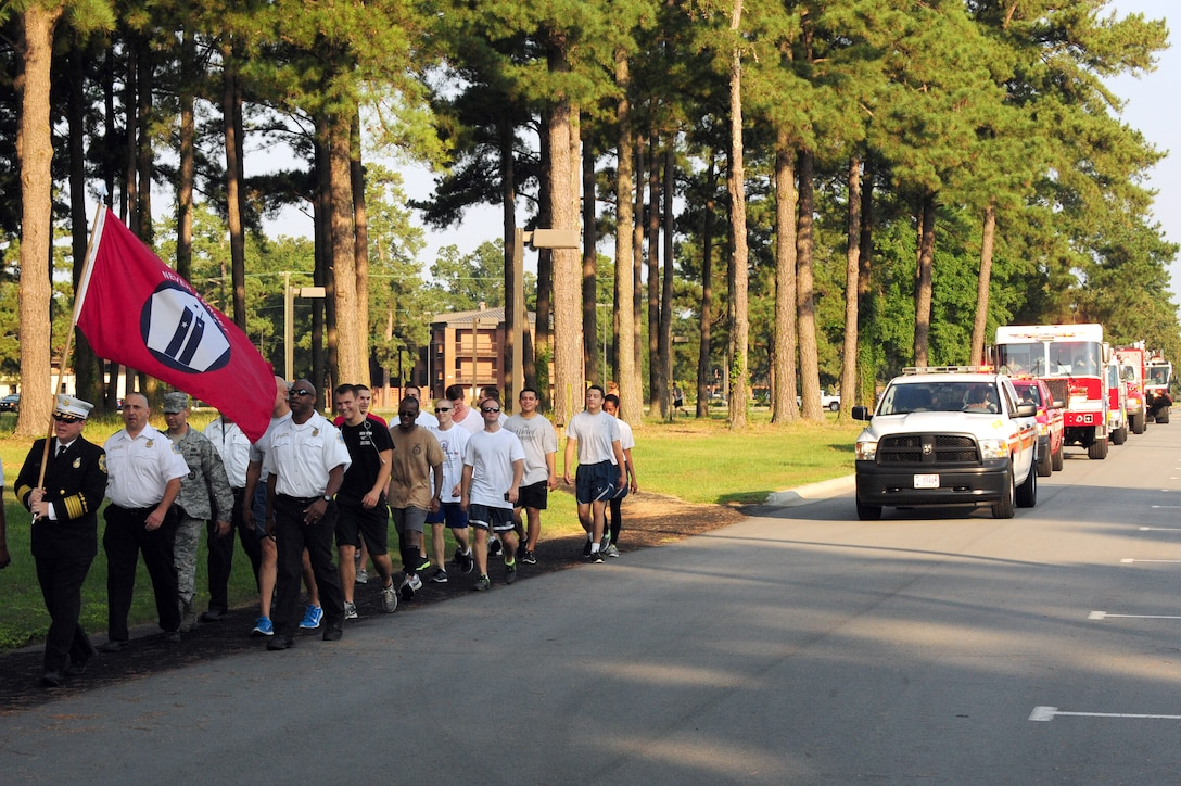 A group of Airmen led by Sean Quinby, 4th Civil Engineer Squadron fire chief, participate in a final march with the 9/11 Remembrance Flag on the two-mile track at Seymour Johnson Air Force Base, N.C., Sept. 12, 2013.  Members of the 4th CES set a goal of 343 miles, which is equivalent to the number of firefighters killed in the line-of-duty during the 9/11 attacks.  Team Seymour bested the goal by more than 1,000 miles.  (U.S. Air Force photo by Airman 1st Class Brittain Crolley)