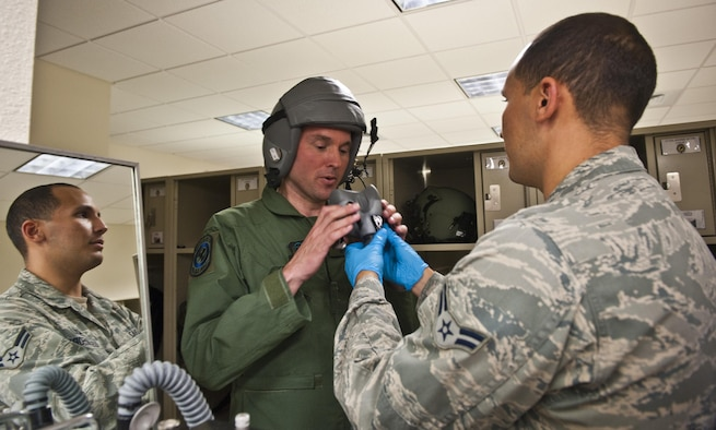 Airman 1st Class Michael Diaz, 4th Special Operations Squadron aircrew flight equipment technician, fits Acting Secretary of the Air Force Eric Fanning's oxygen mask prior to flying on a CV-22 Osprey and AC-130U Spooky at Hurlburt Field Fla., Sept. 9, 2013. The visit is part of Fanning's familiarization with various Air Force missions since becoming the acting secretary.