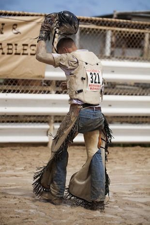 John McDonald, a competitor in a bull riding competition, walks out of the ring after being knocked off early by his bull, Ele Ele, during the inaugural Surf & Turf Buck & Bull Event & Concert at the New Town & Country Stables in Waimanalo, Hawaii, Sept. 7, 2013. (U.S. Marine Corps photo by Lance Cpl. Matthew Bragg)