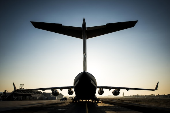 The sun rises above the final U.S. Air Force C-17 Globemaster III, P-223, as crew members arrive at the Boeing plant Sept. 12, 2013, at Long Beach, Calif. The C-17 was flown from California to Joint Base Charleston, S.C.