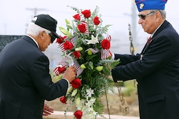Bob Licker, right, holds the wreath for Chosin Few veterans that are placing American flags during the 63rd Anniversary of the Landing on Inchon Memorial Ceremony held at the Chosin Few Monument adjacent to the Pacific Views Event Center here Sept. 13. The ceremony is also a time to commemorate those who gave their life during the conflict. Licker was a once the National President of the Chosin Few Chapter.
