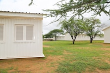 Construction work continues at Dodji Peace Keeping Operations Training Center in Senegal Aug. 20. The camp is being upgraded to include eight new barracks, seen here in white, a dining facility, shower and latrine facilities for men and women, a water treatment plant and a well. Existing barracks remain in the back right. The turnkey facilities will accommodate and supply 1,000 soldiers upon completion mid-September. U.S. Department of State Global Peace Operations Initiative funded the project to support the development of Senegalese PKO capabilities.