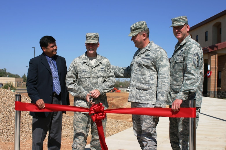 CANNON AIR FORCE BASE, N.M. – (l-r): John Moreno, Albuquerque District chief of Engineering and Construction; Airman Zachariah Mick, 27th Special Operations Maintenance Squadron; Col. Tony Bauernfeind, 27th Special Operations Wing commander, U.S. Air Force; and Chief Master Sgt. Paul Henderson, 27th SOW command chief, watch as Mick prepares to cut the ribbon, officially opening the new 96-person dorm, Sept. 6, 2013.