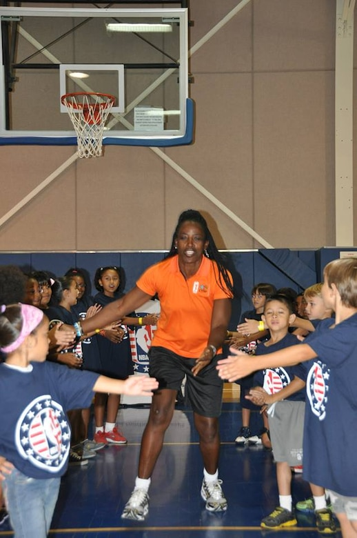 Ruthie Bolton, former Women's National Basketball Association star and two-time Olympic gold medalist, is greeted by military children at March Air Reserve Base, Calif., during the NBA Cares Hoops for Troops basketball clinic Sunday, Sept. 8, 2013. The NBA Cares program sponsored the event in conjunction with the Healthy Base Initiative kickoff. (U.S. Air Force photo/Master Sgt. Linda Welz)