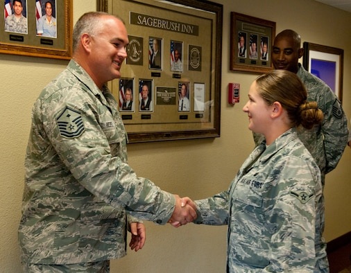 U.S. Air Force Master Sgt. Kelly Riedel, 366th Medical Group first sergeant, coins an Airman, Aug 20, 2013 at Mountain Home Air Force Base, Idaho. Riedel was so impressed with her motivation with volunteering that he presented her with a first sergeants coin. (U.S. Air Force photo by Airman 1st Class Brittany Chase/Released)