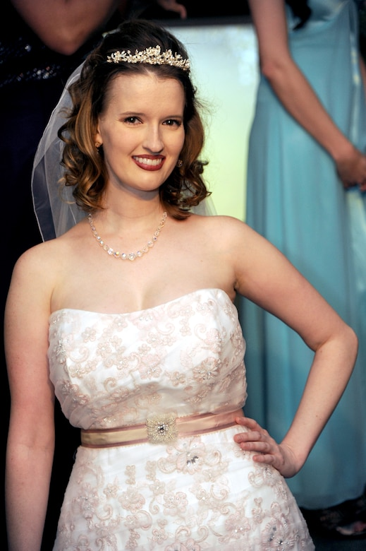 Charly Swiger-Peterson, fashion show model, strikes a pose in a Cinderella's Closet wedding dress at the closing of the B-2 Fabulous Fashion Show at Whiteman Air Force Base, Mo., Sept. 6, 2013. Donations of dresses, shoes and jewelry are always accepted at the Cinderella's Closet, and can be made at the Airman's Attic, open Tuesdays and Fridays from 10 a.m. to 2 p.m. (U.S. Air Force photo by Airman 1st Class Shelby R. Orozco/Released)