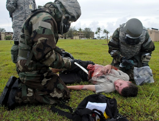 Airmen perform exercise scenario self-aid buddy care during the Ability to Survive and Operate Rodeo Sept. 13, 2013, on Andersen Air Force Base, Guam. Exercise evaluation team members graded participants on their ability to demonstrate wartime skills in preparation for real-world contingencies throughout the rodeo.  (U.S. Air Force photo by Airman 1st Class Amanda Morris/Released)