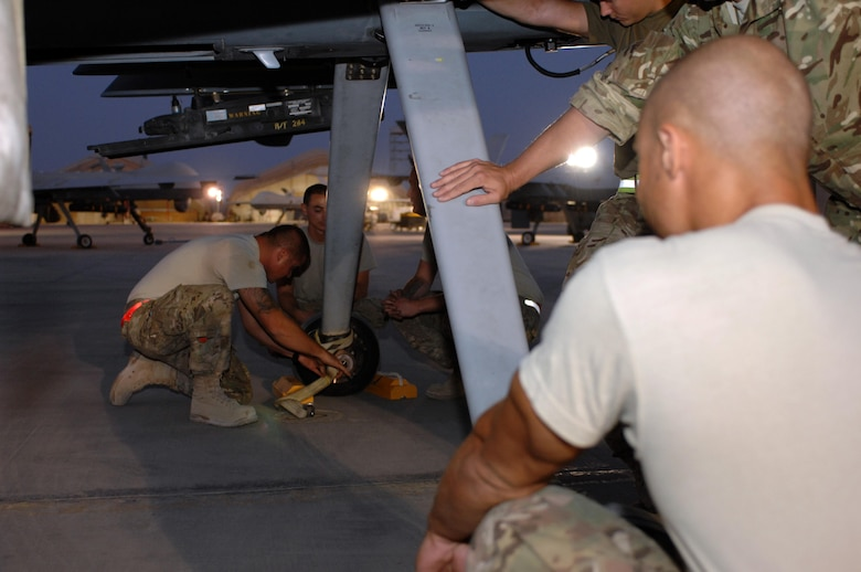 Airmen from the 451st Expeditionary Aircraft Maintenance Squadron secure an MQ-9 Reaper in preparation for a mission Aug. 27, 2013 at Kandahar Airfield, Afghanistan. Members of the 451st EAMXS are responsible for maintenance, launch and recovery for MQ-1 and MQ-9 aircraft.