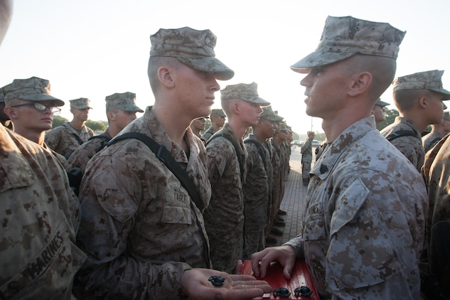 Sgt. Joseph Boucher, a drill instructor of Platoon 1068, Delta Company, 1st Recruit Training Battalion, presents Rct. Dylan Yagle with an Eagle, Globe and Anchor during the emblem ceremony Sept. 7, 2013, at the Iwo Jima flag raising statue on Parris Island, S.C. This is the first time drill instructors such as Boucher, a 27-year-old native of Kingston, N.H., call their recruits Marines. Yagle, an 18-year-old native of Fort Mill, S.C., is the third Marine in his family, following in the footsteps of his brother, Capt. Austin Yagle, and his father, Andrew Yagle, a retired sergeant major. Delta Company is scheduled to graduate Sept. 13, 2013. Parris Island has been the site of Marine Corps recruit training since Nov. 1, 1915. Today, approximately 20,000 recruits come to Parris Island annually for the chance to become United States Marines by enduring 13 weeks of rigorous, transformative training. Parris Island is home to entry-level enlisted training for 50 percent of males and 100 percent for females in the Marine Corps. (Photo by Lance Cpl. MaryAnn Hill)