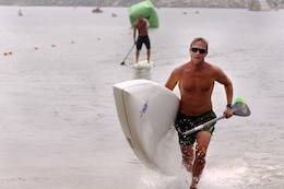 Mark Quest, 41, charges the beach as he completes one of three miles of the Age Group Amphibious Assault Stand-up Paddleboard race during the Water Warrior Beach Festival at Del Mar beach here, Sept. 14.