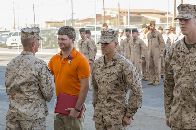 Former Cpl. Matthew Eason, in orange, who served as a powerline mechanic from Marine Attack Squadron 211 and is a native of Hattiesburg, Miss., receives a Purple Heart from Lt. Col. Cory Simmons, left, the commanding officer of VMA-211, for the wounds he received while defending against a Taliban attack at Camp Bastion, Afghanistan, on Sept. 14, 2012. Standing next to Eason are VMA-211 Marines Sgt. Jonathan Cudo, center-right, a powerline mechanic, and Lance Cpl. Cole Collums, right, an aviation electronics technician, who also received Purple Hearts at this ceremony at the squadron hangar on Marine Corps Air Station Yuma, Ariz., Aug. 1.