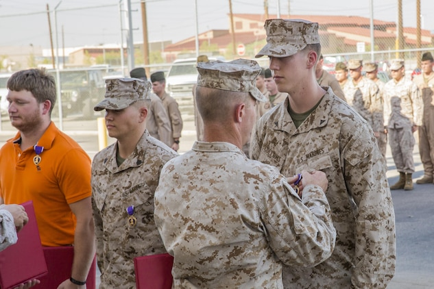 Lance Cpl. Cole Collums, right, an aviation electronics technician from Marine Attack Squadron 211, and a native of Mountainburg, Ark., receives a Purple Heart from Lt. Col. Cory Simmons, center-right, the commanding officer of VMA-211, for the wounds he received while defending against a Taliban attack at Camp Bastion, Afghanistan, on Sept. 14, 2012. Standing next to Collums are VMA-211 Marines Sgt. Jonathan Cudo, center-left, a powerline mechanic, and former Cpl. Matthew Eason, left, a powerline mechanic, who also received Purple Hearts at this ceremony at the squadron hangar on Marine Corps Air Station Yuma, Ariz., Aug. 1.