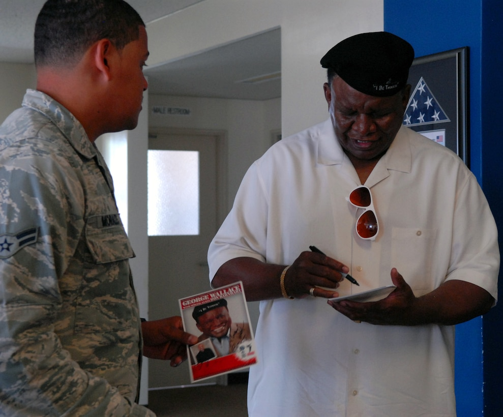 Comedian George Wallace signs an autograph for an 18th Security Forces Squadron Airman during a squadron visit on Kadena Air Base, Japan, Sept. 6, 2013. Wallace flew from Las Vegas to visit overseas troops and performed two free shows on Okinawa during USO?s Celebrity Comedy Tour.  (U.S. Air Force photo by Staff Sgt. Lauren Snyder)
