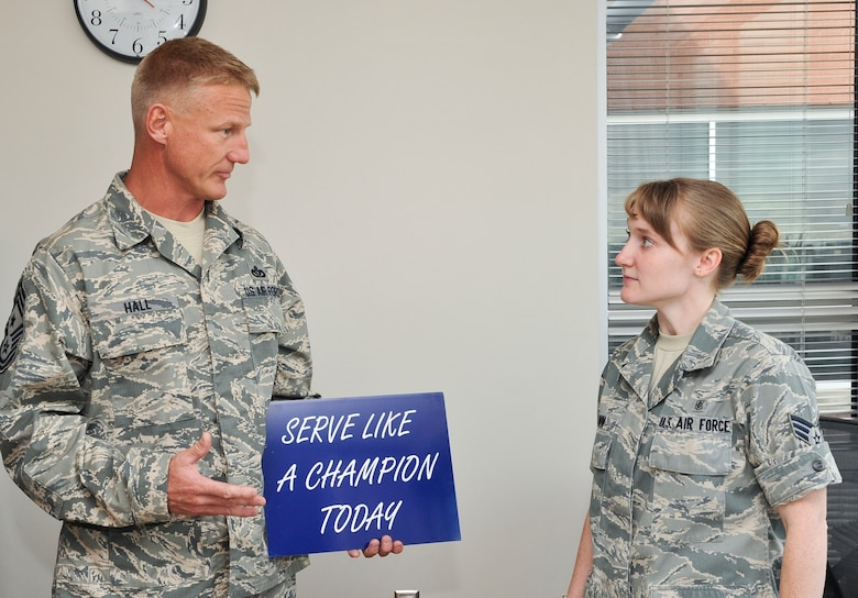 Senior Airman Regina Brown, 460th Medical Group allergy immunization technician, receives a recognition award from Chief Master Sgt. Craig S. Hall, 460th Space Wing command chief, Sept. 16, 2013, at the Veterans Affairs Joint Venture Buckley Clinic in Aurora, Colo. Brown received this award for demonstrating excellent morals and service. This is the first award Hall has given that rewards and encourages members of Team Buckley to serve like a champion. (U.S. Air Force photo by Senior Airman Phillip Houk/Released)