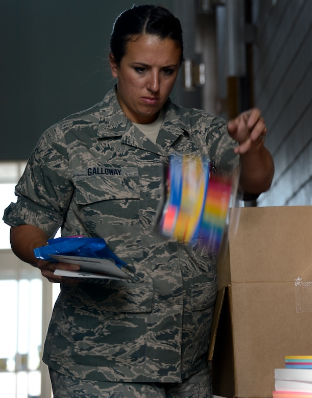 Master Sgt. Crystal Galloway, 133rd Maintenance Operations Flight, tosses makers into the pile for donation in St. Paul, Minn., Aug. 15, 2013. The school supplies were donated from customers at Dollar Trees stores throughout the Twins Cities area in support of Operation Homefront and the Back-to-School-Brigade.    (U.S. Air National Guard photo by Tech. Sgt. Amy M. Lovgren/ Released)