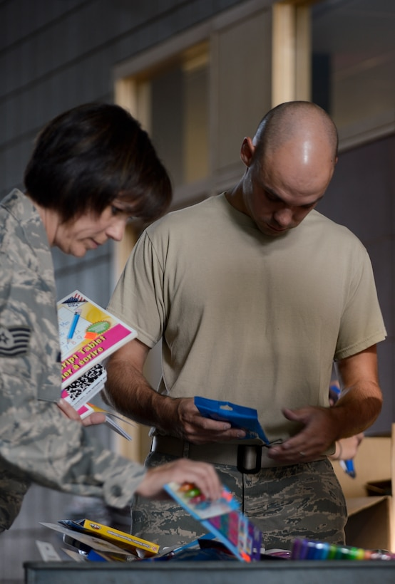 Tech. Sgt. Victoria Christian, left, from the 133rd Maintenance Squadron, and Master Sgt. Aaron Bayer, right, 133rd Flight Support Squadron, separate donated school supplies for distribution in St. Paul, Minn., Aug. 15, 2013. The school supplies were donated from customers at Dollar Trees stores throughout the Twins Cities area in support of Operation Homefront and the Back-to-School-Brigade.    (U.S. Air National Guard photo by Tech. Sgt. Amy M. Lovgren/ Released)