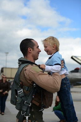 SPANGDAHLEM AIR BASE, Germany – U.S. Air Force Capt. Lance Ferguson, 480th Fighter Squadron pilot from Adrian, Mich., celebrates with his son, Liam during a deployment homecoming Sept 15, 2013. The 480th FS maintains ready forces to conduct a full range of operations in real-world scenarios. (U.S. Air Force photo by Airman 1st Class Gustavo Castillo/Released)