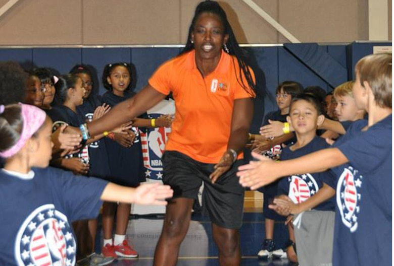 Ruthie Bolton, former Women's National Basketball Association star and two-time Olympic gold medalist, is greeted by military children at March Air Reserve Base, Calif., during the NBA Cares Hoops for Troops basketball clinic Sept. 8, 2013. The NBA Cares program sponsored the event in conjunction with the Healthy Base Initiative kickoff. (U.S. Air Force photo/Master Sgt. Linda Welz)