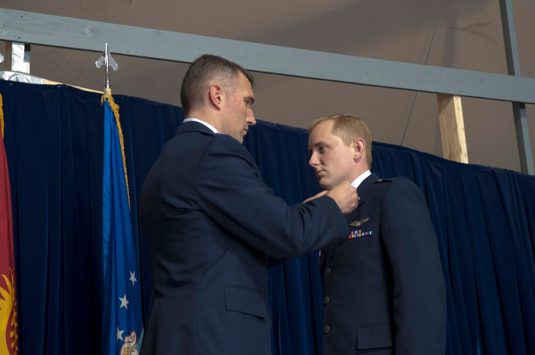 Lt.Col. James Mach, 22nd Expeditionary Air Refueling Squadron commander, pins the rank of captain onto Capt. Norman Popp, 22 EARS pilot, during a 376th Air Expeditionary Wing promotion and awards ceremony at Transit Center at Manas, Kyrgyzstan, August 31, 2013. The rank has been passed down through U.S. combat zones and conflicts since World War II. Popp is deployed out of RAF Mildenhall, England, and is a native of Jackson, Mo.(U.S. Air Force photo/Staff Sgt. Robert Barnett)