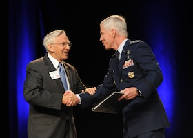 Jerry White presents Gen. William L. Shelton a book on behalf of the Air Force Association Sept. 17, 2013, at the Air Force Association's 2013 Air & Space Conference and Technology Exposition in Washington, D.C. The conference is a professional development event sponsored and conducted by AFA in support of the total Air Force. White is the vice chairman of the board and Shelton is the commander of Air Force Space Command. (U.S. Air Force photo/Airman 1st Class Aaron Stout)