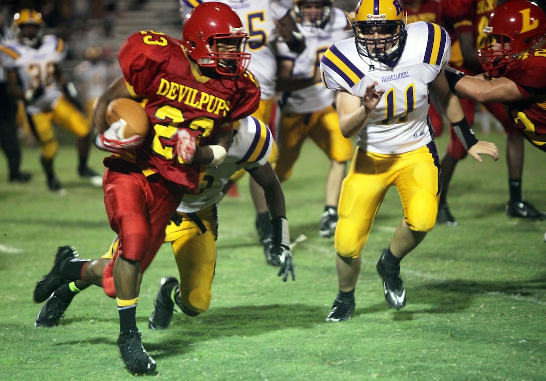 Jamaz Richardson, Lejeune High School's starting running back, bolts past a Rosewood High School defender aboard Marine Corps Base Camp Lejeune, Friday. Richardson ran for 173 total yards during the game and scored four touchdowns for the Devilpup football team.