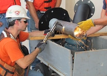 A welder uses a cutting torch to trim an intake pipe for the hydro plant.