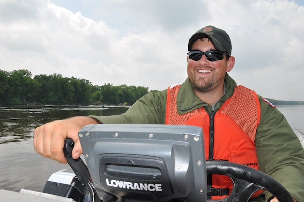 Dan Reburn, operations, drives a boat to a Mississippi River island near Red Wing, Minn., June 10.