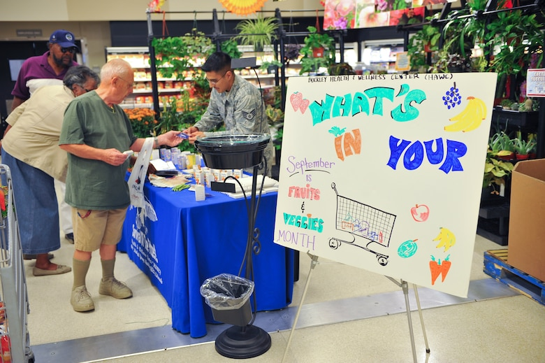Commissary shoppers receive information from Staff Sgt. Carlos Avalos, 460th Medical Group diet technician, Sept. 18, 2013, at the commissary on Buckley Air Force Base, Colo. The Buckley Health and Wellness Center outreach program is part of Fruit and Veggie Month, encouraging people to eat healthy and learn about different types of food. (U.S. Air Force photo by Senior Airman Phillip Houk/Released)