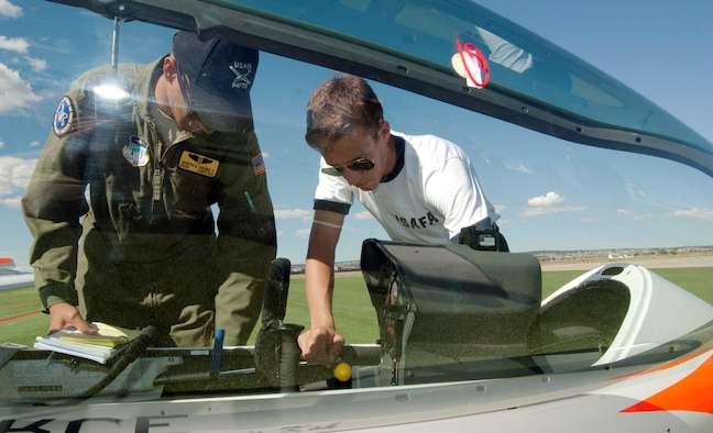 Cadet 2nd Class Joseph Goode IV and Cadet 3rd Class Adam Marcinkowski conduct a preflight check on a TG-16A glider at the Air Force Academy Airfield Sept. 17, 2013. The checks ensure the instruments are set correctly, that the glider's internal systems have the correct voltage and that safety restraints are in good condition. This marked the first solo flight for Marcinkowski, who is assigned to Cadet Squadron 30. (U.S. Air Force photo/Don Branum)