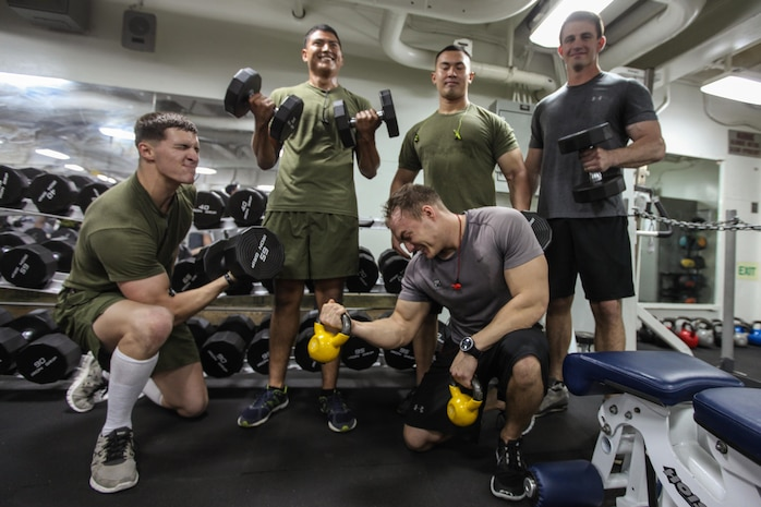 """USS BONHOMME RICHARD, At Sea – Marines with the 31st Marine Expeditionary Unit pause their workout to pose for a """"meathead"""" group photo here, Sept. 13.   Physical training gives Marines more than just bulging biceps, it serves as an outlet for anger, keeps an anxious mind occupied and builds unit camaraderie through shared pain and success. (Marine Corps photo by Sgt. Paul Robbins)"""