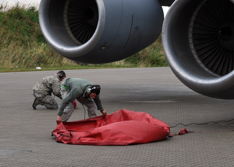 """2nd Lt. Christopher Hickman, left, and Staff Sgt. Curtis McKee, 100th Air Refueling Wing, remove engine covers on a KC-135R Stratotanker prior to its disembarkment Sept. 16, 2013, for the Arctic Challenge exercise """"play zones"""" over northern Norway. The 100th ARW provided all the aerial refueling for the exercise."""