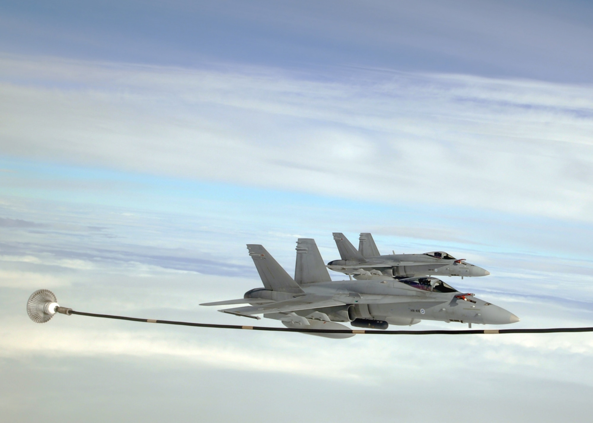 """Two Finnish Air Force F-18C Hornets prepare to refuel with a U.S. Air Force KC-135R Stratotanker Sept. 17, 2013, over Norway during the Arctic Challenge exercise. The Hornets formed a """"Red Team"""" strike package with six F-15E Strike Eagles from the 48th Fighter Wing as they attempted to """"raid"""" an enemy command post during this portion of the exercise."""