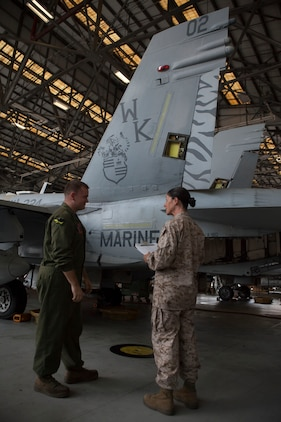 """Staff Sgt. Christine Mendenhall, 2nd Marine Aircraft Wing refrigeration electrician mechanic inspector from Newark S.C., discusses safety protocols with Sgt. Tony Yates, Marine All-Weather Fighter Attack Squadron 224 hydraulic, pneumatic, structures mechanic from Covington Ky., during an Aviation Logistics Management Assist Team (ALMAT) evaluation aboard the Air Station Sept., 10. The squadron achieved an """"on track"""" rating from the team of experts who examined and graded more than 40 programs within VMFA(AW) 224 and trained Marines on areas needing improvement."""