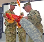 Col. Matthew Lewis, left, and Command Sgt. Maj. Jason Werner, right, commander and senior NCO, TF Demons, CAB, respectively, assume responsibility of Army aviation operations in RC-South, Southwest and West by unfurling the unit colors during a Sept. 3 transfer of authority ceremony at Kandahar Airfield, Afghanistan.  Photo by: Capt. Andrew Cochran, CAB.