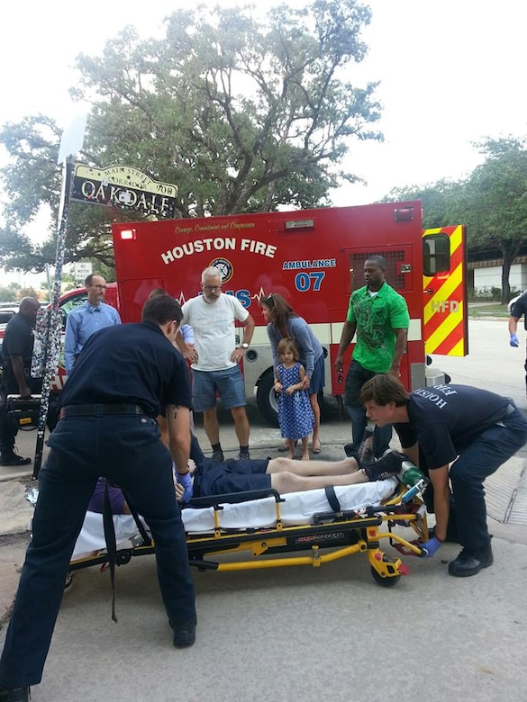 (In green) Air Force Staff Sgt. Robert Niter III, 47th Medical Operations Squadron NCO in charge of optometry, looks on as members from the Houston Fire Department prepare to load a patient into their ambulance Sept. 12, 2013, in Houston. Niter, was on leave, when he noticed a downed-man with a crowd of people around him while driving that afternoon. Niter and his girlfriend immediately responded to the man before beginning life saving techniques for nearly 30 minutes until emergency management services arrived. The unknown man was stabilized and is doing well, according to the HFD, all due to Niters selfless actions. (Courtesy photo)