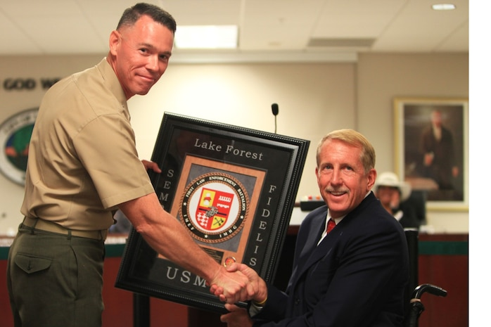Lt. Col. Jan Durham, commanding officer of 1st Law Enforcement Battalion, presents a plaque of appreciation to Scott Voigts, mayor of Lake Forest. The city of Lake Forest voted unanimously to adopt 1st Law Enforcement Battalion in Lake Forest, Calif., Sept. 17.