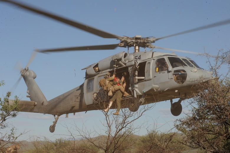 A pararescue jumper and a pilot with a simulated injury are hoisted up to a U.S. Navy MH-60S Knighthawk helicopter during a field training exercise Sept. 18, 2013 in southern Arizona.  The exercise was part of joint training with the U.S. Air Force A-10 Thunderbolt squadrons and Rescue units of Davis-Monthan Air Force Base, Ariz. and the MH-60S Knighthawks of the Helicopter Sea Combat Squadron 23, Naval Air Station North Island, Calif. (U.S. Air Force photo by Airman 1st Class Chris Massey/Released))