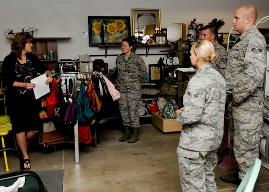 Brenda Eiman, B-One Yard Thrift and Consignment Store manager, explains the many items and resources available to Airmen during a tour of the B-One Yard Thrift and Consignment store at Ellsworth Air Force Base, S.D., Sept. 17, 2013. The store offers eligible Airmen resources ranging from the Airman's Attic – a loan closet offering necessary household items to the Car Seat Program – which provides Airmen one free convertible infant car seat per child. (U.S. Air Force photo by Airman 1st Class Anania Tekurio/Released)