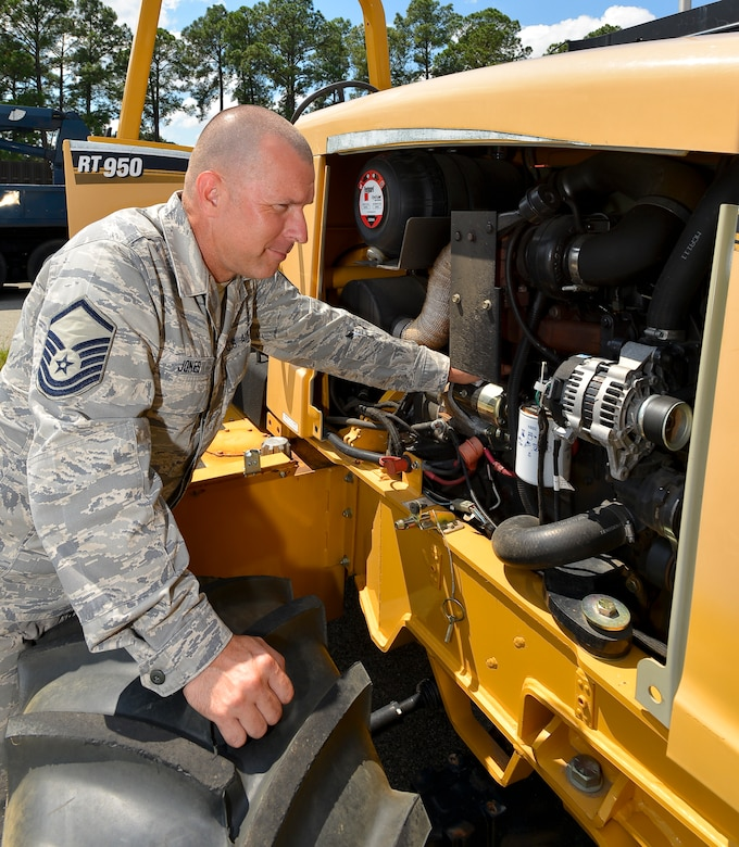 U.S. Air Force Master Sgt. Andrew Jones, a heavy mobile maintenance mechanic with the 202nd Engineering Installation Squadron, Georgia Air National Guard, inspects the engine on a trencher, Robins Air Force Base, Ga., Sept. 10, 2013. Working as a dual-status civil service technician, Jones is responsible to ensure all vehicles and heavy equipment used by the squadron is mission ready at all times. (U.S. Air National Guard photo by Tech Sgt. Regina Young/Released)