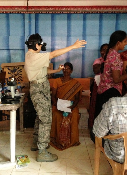 Air Force Lt. Col. Thuy Tran, 142nd Fighter Wing Medical Group, performs optometry examinations with a patient during the Pacific Angel Mission in the Jaffna Peninsula of Sri Lanka, July 28- Aug.18. (Photo courtesy of Tech. Sgt. Misty Ray, 142nd Fighter Wing Medical Group).