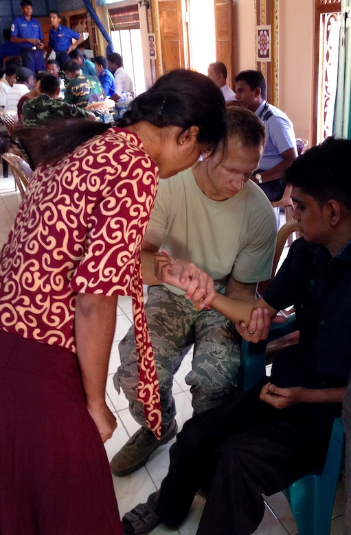 Air Force Maj. Eric Stephan examines a patient during the Pacific Angel Mission with the assistance of translator in the Jaffna Peninsula of Sri Lanka, July 28- Aug.18. (Photo courtesy of Tech. Sgt. Misty Ray, 142nd Fighter Wing Medical Group).