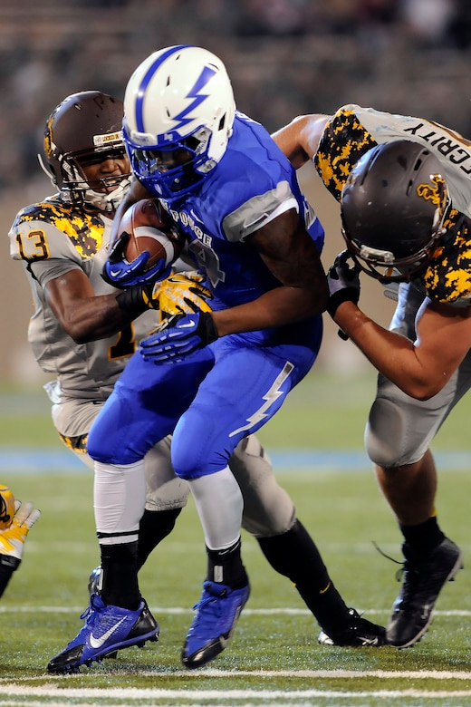 Junior running back Jon Lee gets wrapped up by two Wyoming defenders during the Air Force-Wyoming game at Falcon Stadium Sept. 21, 2013. Lee had eight carries for 82 yards in the Falcons' 56-23 loss to the Cowboys. (U.S. Air Force photo/Sarah Chambers)