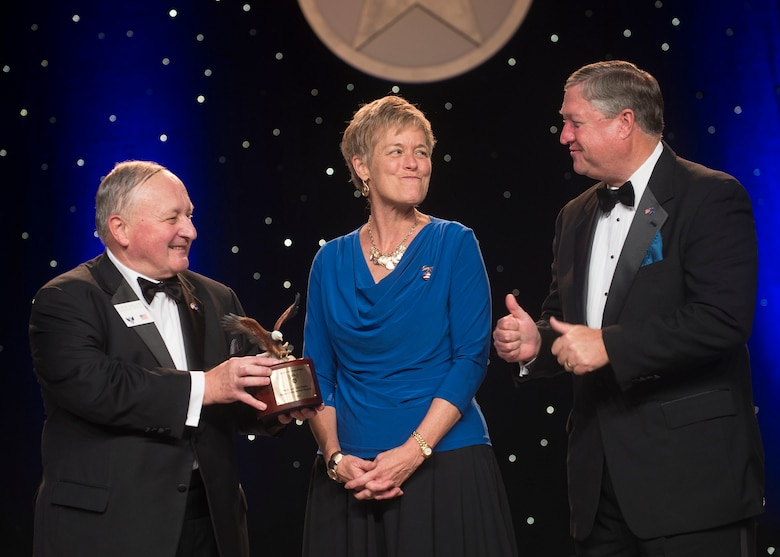 Former Secretary of the Air Force Michael Donley (right) looks on as his wife Gail (center) shows her surprise after the Air Force Association's Chairman of the Board George Muellner (left) announced the new Mike and Gail Donley Special Scholarship Program during the United States Air Force Anniversary Dinner Sept. 18, 2013, at the National Harbor, Washington, D.C. The dinner celebrated the 66th Anniversary of the Air Force during the Air Force Association's 2013 Air & Space Conference and Technology Exposition. AFA sponsors the annual conference to promote professional development in support of the total Air Force. (U.S. Air Force photo/Jim Varhegyi)